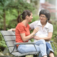 Senior woman with carer sitting on bench at the park